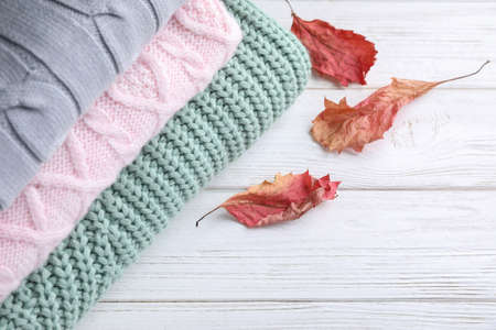 Stack of soft knitted sweaters on white wooden table, closeup Stock Photo
