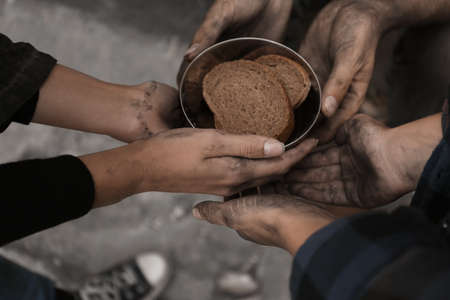 Poor homeless people with pieces of bread outdoors, closeup