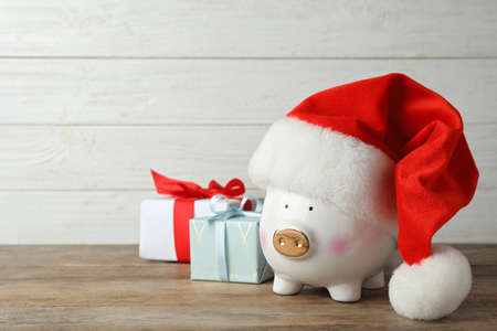 Piggy bank with Santa hat and gift boxes on wooden table. Space for text Stockfoto