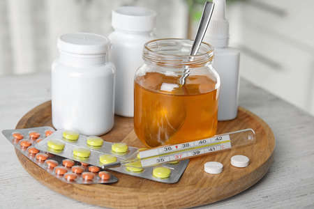 Honey and different cold remedies on white wooden table