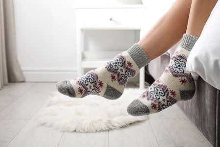 Frau trägt gestrickte Socken auf dem Bett drinnen, Nahaufnahme. Warme Kleidung