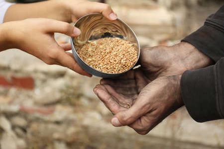 Woman giving poor homeless man bowl of wheat outdoors, closeup