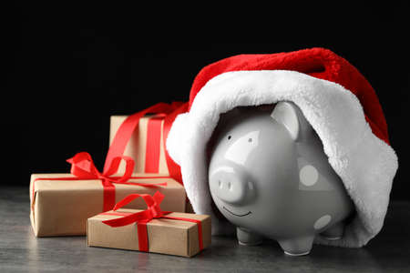 Piggy bank with Santa hat and gift boxes on grey table against black background Stockfoto