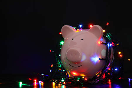 Piggy bank with Christmas lights on wooden table against black background. Space for text