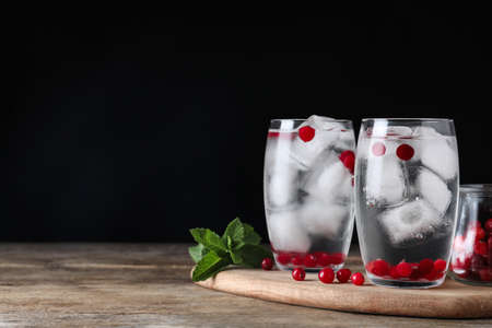 Glasses of cocktail with vodka, ice and cranberry on wooden table against black background. Space for text