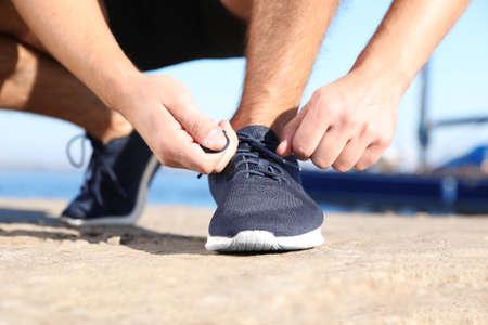 Sportlicher Mann, der Schnürsenkel bindet, bevor er im Freien läuft Standard-Bild