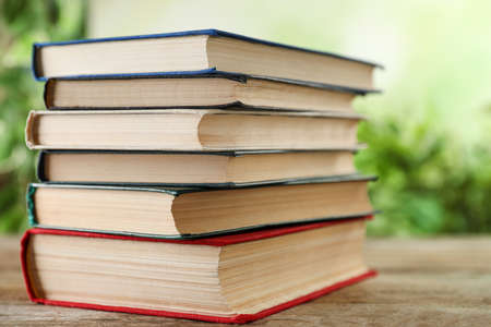 Stack of hardcover books on wooden table against blurred background