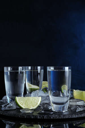 Vodka in shot glasses and lime slices on dark background
