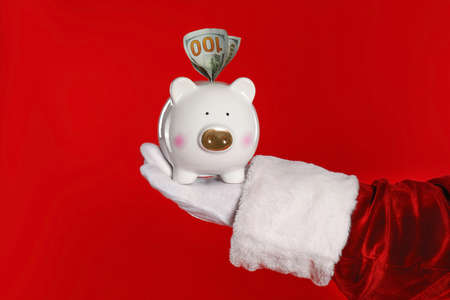 Santa Claus holding piggy bank with dollar banknotes on red background, closeup