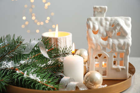 Composition with house shaped candle holder on grey table against blurred background. Christmas decoration