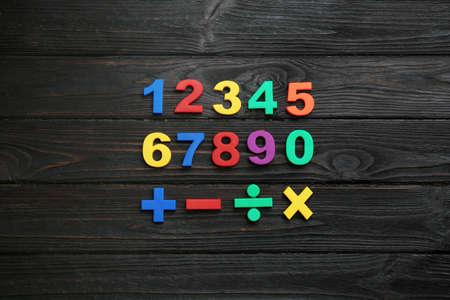 Colorful magnetic numbers and math symbols on black wooden background, flat lay