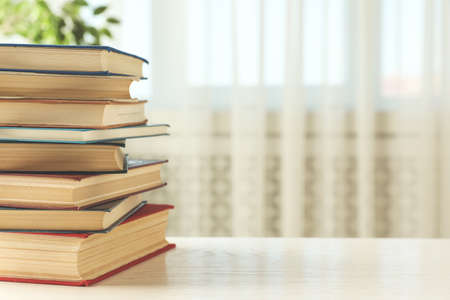 Stack of hardcover books on white wooden table indoors. Space for text
