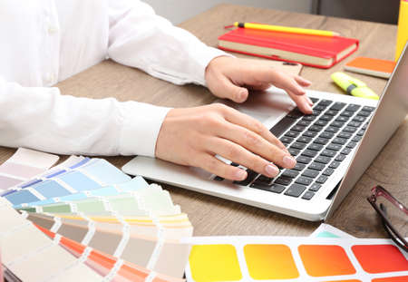 Woman working with laptop and palette samples at wooden table, closeup Banque d'images