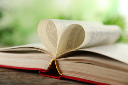 Heart made of book pages on wooden table against blurred background, closeup