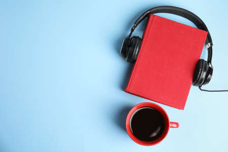 Modern headphones with hardcover book and coffee on light blue background, top view. Space for text