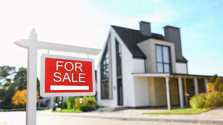 Cartello rosso immobiliare vicino alla casa all'aperto in giornata di sole