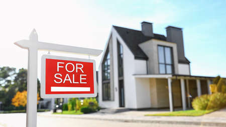 Signe immobilier rouge près de la maison à l'extérieur par beau temps