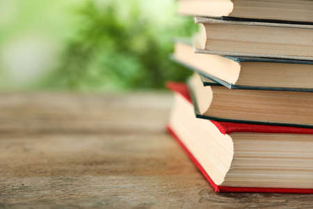 Stack of hardcover books on wooden table against blurred background, closeup. Space for text