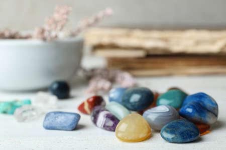 Montón de diferentes piedras preciosas en la mesa de madera blanca. Espacio para texto