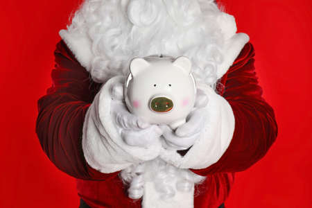 Santa Claus holding piggy bank on red background, closeup Stockfoto