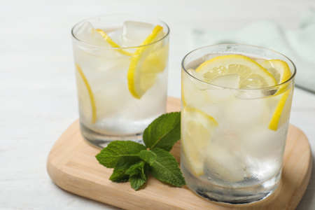 Glasses of cocktail with vodka, ice and lemon on white wooden table