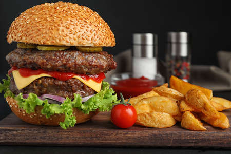 Delicious burger with meat cutlets on black table Stockfoto