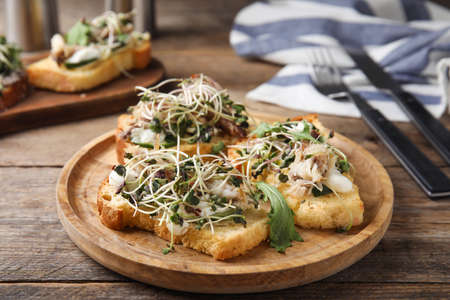 Delicious bruschettas with fish on wooden table Stockfoto