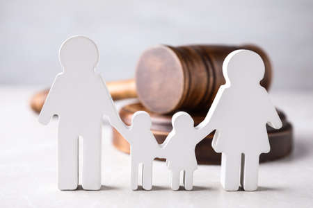 Figure in shape of people and wooden gavel on light table. Family law concept 스톡 콘텐츠