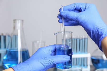 Medico mescolando liquido con bacchetta di vetro, primo piano. Analisi di laboratorio