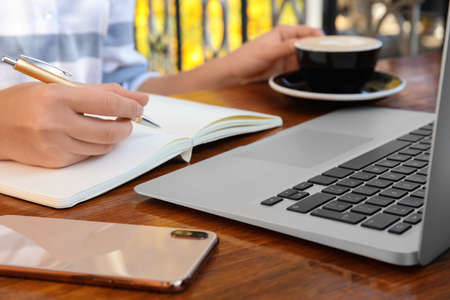 Woman writing blog content in notebook at table, closeup