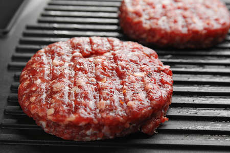 Raw meat cutlets for burger on grill, closeup