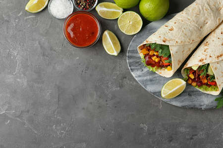 Board with delicious meat tortilla wraps on grey table, flat lay. Space for text