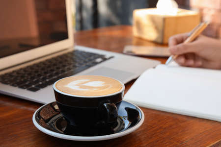 working at table in cafe, focus on cup of coffee