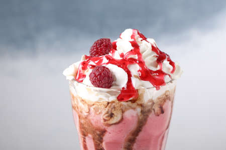 Tasty milk shake with topping on color background, closeup Stock fotó
