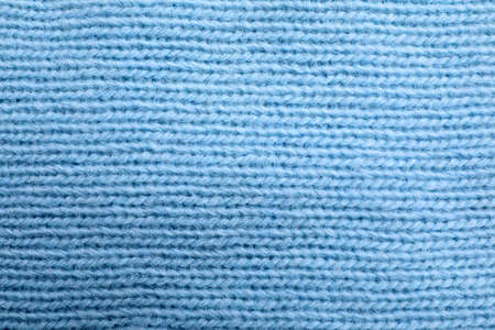 Light blue knitted sweater as background, closeup view