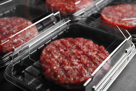 Plastic containers with raw meat cutlets for burger on table, closeup