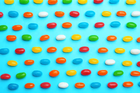 Tasty colorful jelly beans on blue background, flat lay