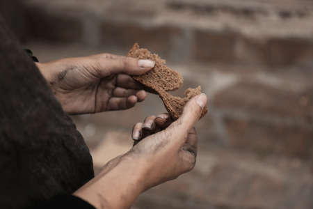 Poor homeless with piece of bread outdoors, closeup Stock Photo