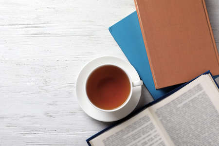 Hardcover books and cup of tea on white wooden table, flat lay