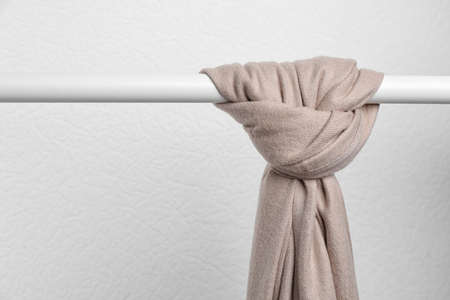 Brown scarf on wardrobe rack against light background, space for text. Autumn clothes Banque d'images