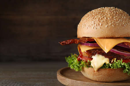 Plate with juicy bacon burger on wooden table. Space for text Stockfoto