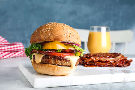 Fresh juicy bacon burger on marble table Stockfoto