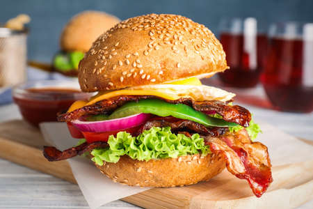 Fresh juicy bacon burger on white wooden table