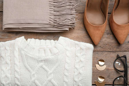 Flat lay composition with warm clothes on wooden background