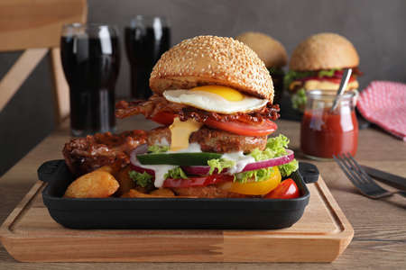 Serving pan with juicy bacon burger on wooden board Stockfoto