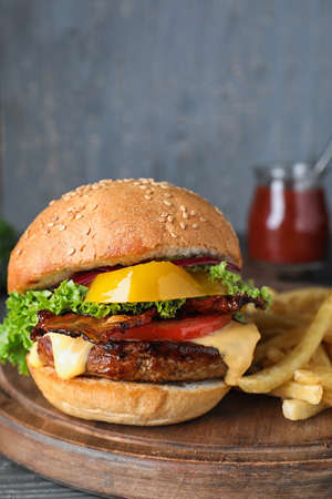 Fresh juicy bacon burger on wooden board against grey background