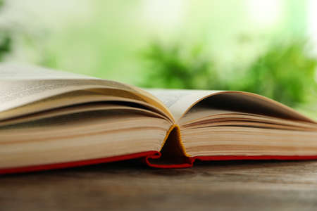 Open hardcover book on wooden table against blurred background closeup