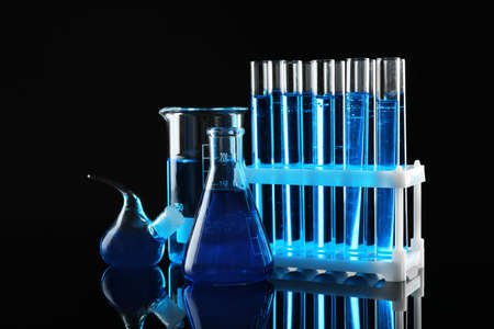 Laboratory glassware with blue liquids on black background