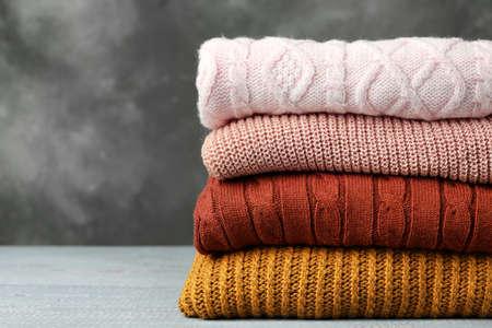 Stapel warme kleren op houten tafel tegen een grijze achtergrond. Herfstseizoen Stockfoto