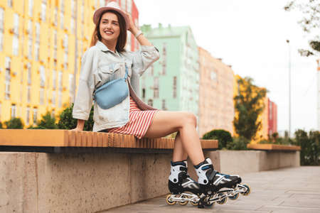 Beautiful young woman with roller skates sitting on bench outdoors